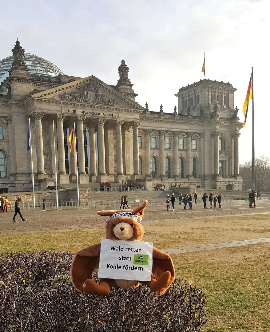 Das Photo zeigt Stofffledermaus Plüti vor dem Reichstag in Berlin 2018 mit der Botschaft: Stoppt die Braunkohle! // the photo shows soft toy bat Plüti in front of the Parlament Building in Berlin 2018 with his message to end coal